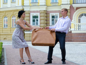 Stylish young couple fighting over luggage and playing tug of war with a large suitcase on an urban street