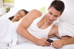 Woman sleeping next to Man texting